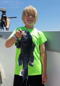 Reeling in Black Fish on Black Hawk Party Fishing Boat